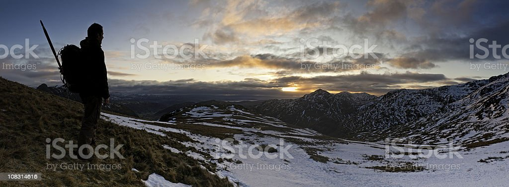 Hiker watching mountain sunrise golden clouds white snow peaks panorama stock photo