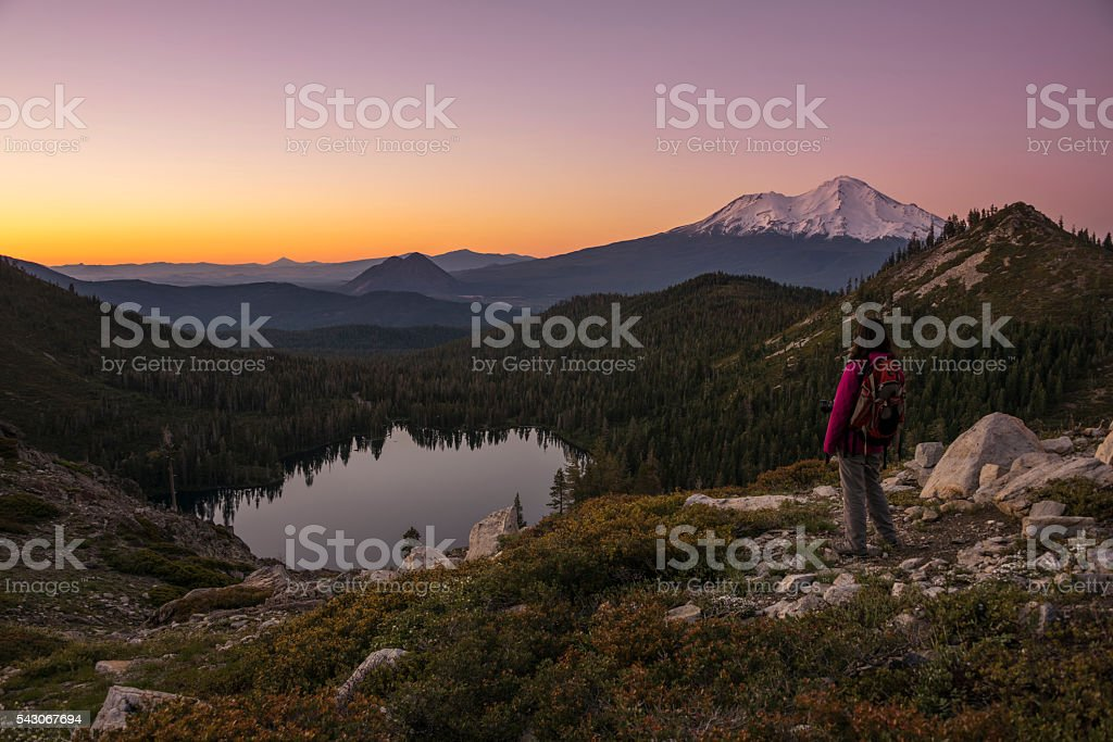Hiker watching sunset on the mountain. stock photo