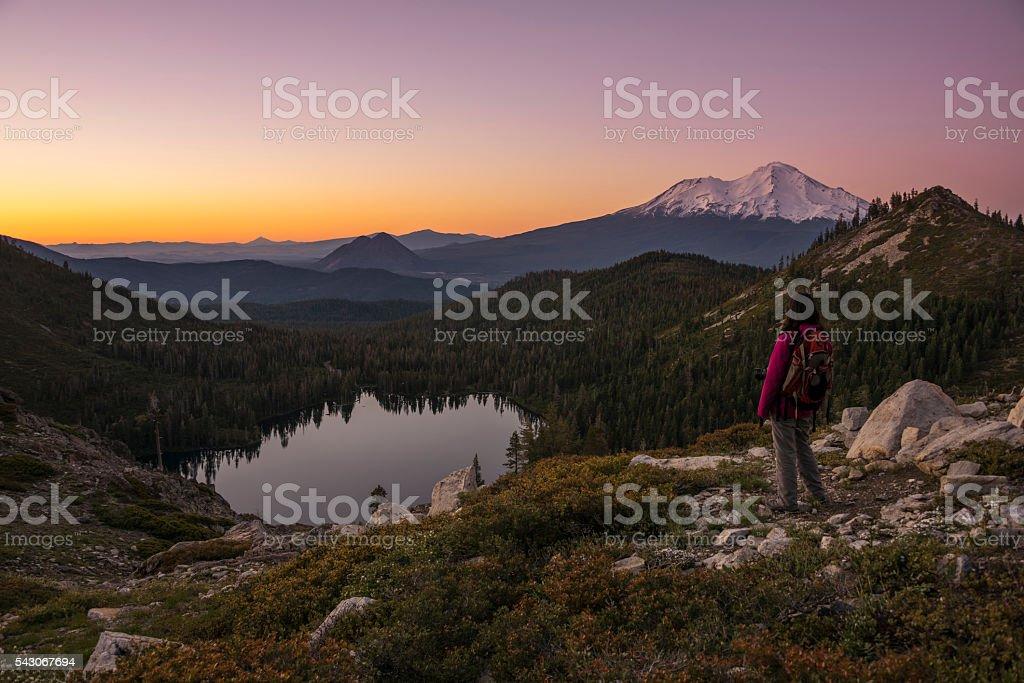 Hiker watching sunset on the mountain. stock photo
