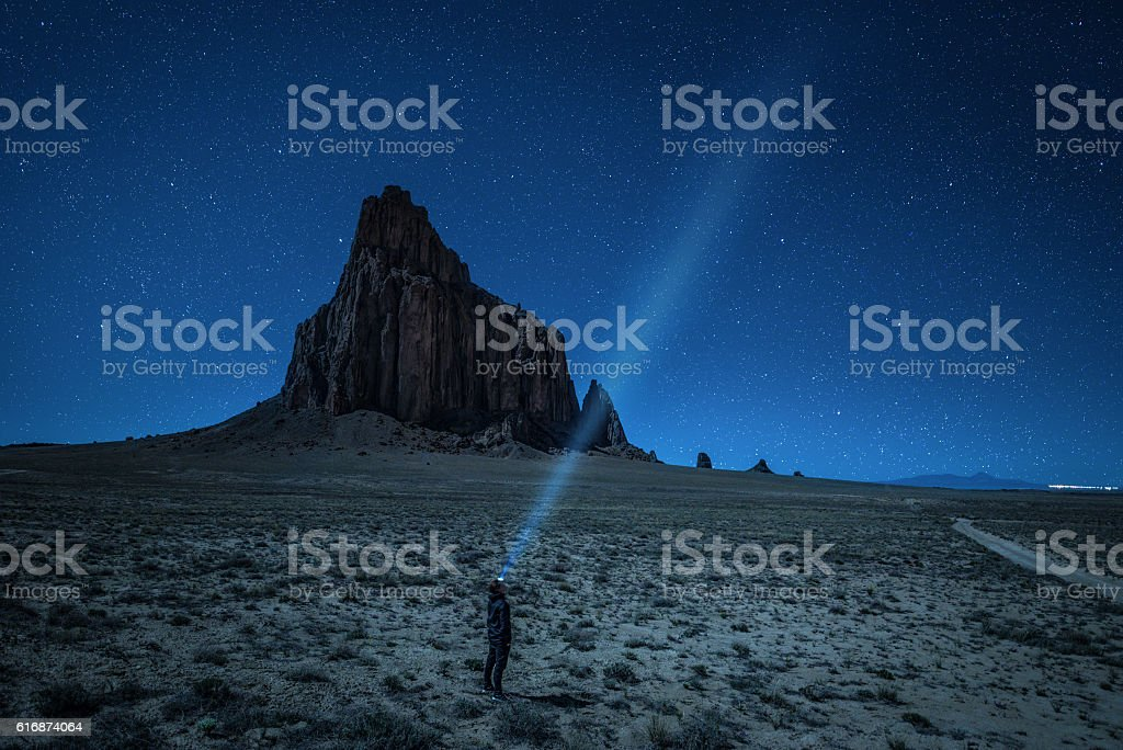Hiker with a head lamp under the night sky stock photo