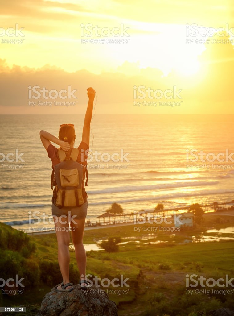 Hiker with backpack enjoying sunset on top of a mountain stock photo