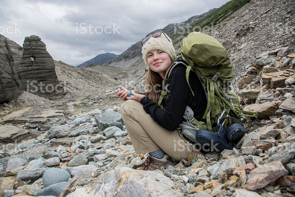 Hiker with Backpack holding her Mobile Phone in the Mountains stock photo