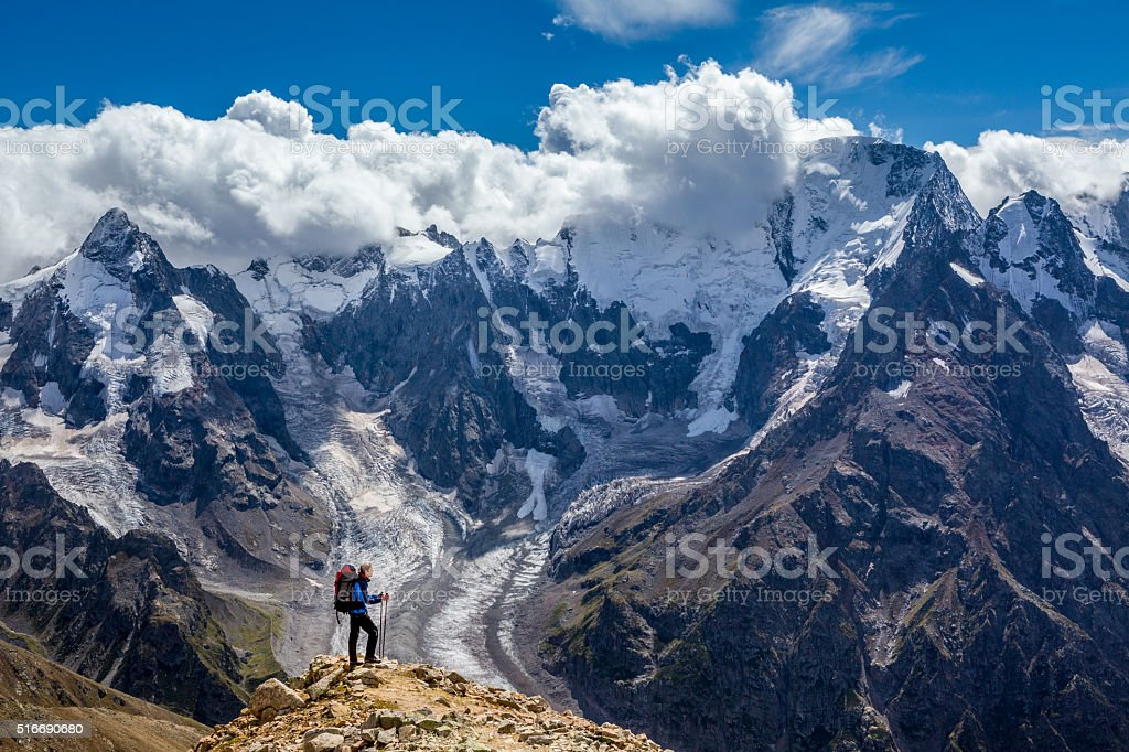 Hiker with backpack standing on mountain top and enjoying scene stock photo