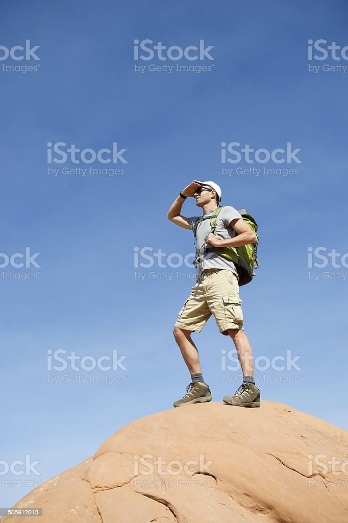 Hiker with Backpack Standing Outdoors on Rock stock photo