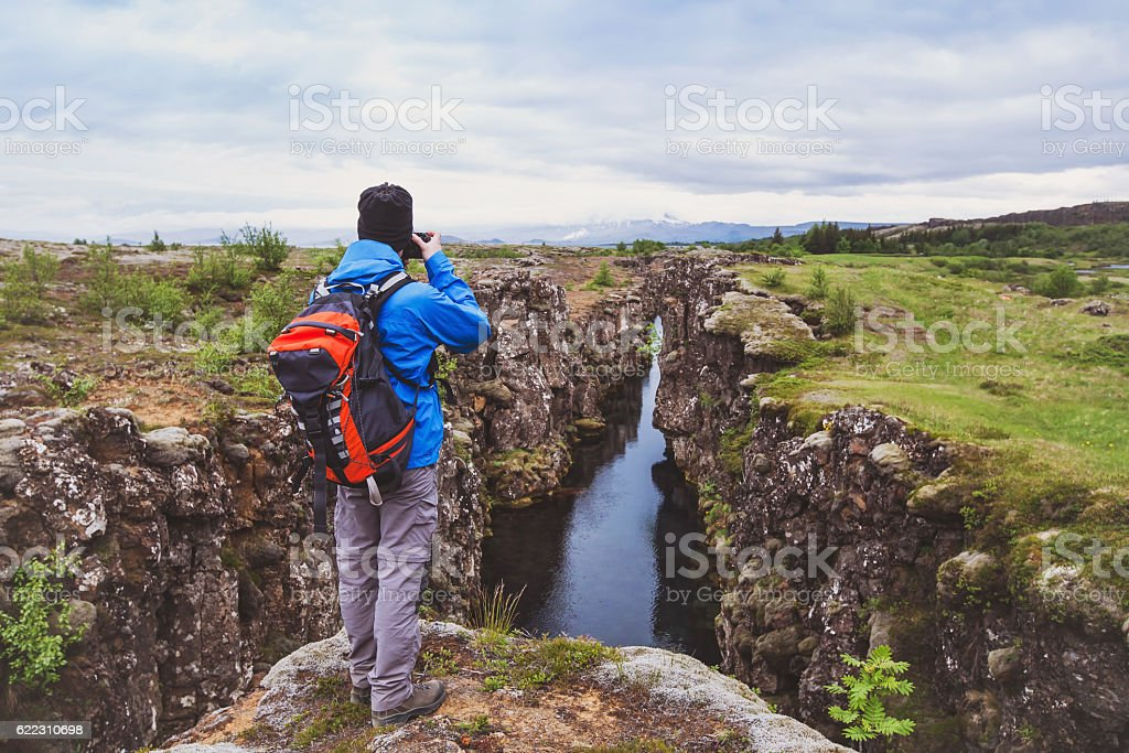 hiker with backpack taking photo of beautiful landscape in Iceland stock photo