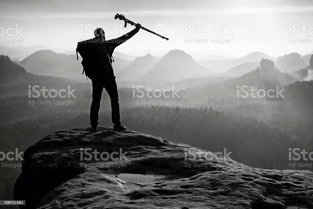 Hiker with broken leg in immobilizer. Deep valley bellow silhouette stock photo