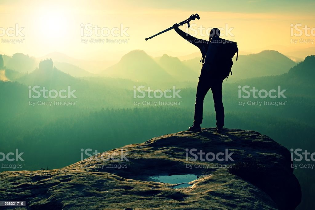 Hiker with crutch above head. Deep valley bellow man silhouette stock photo