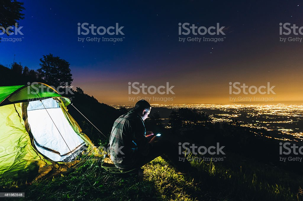 Hiker with device camping at night stock photo
