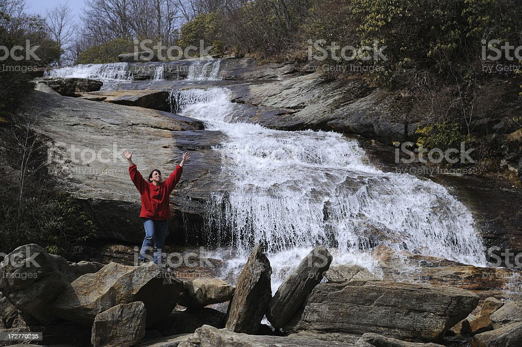 Hiker With Hands in Air Next To Waterfall royalty-free stock photo