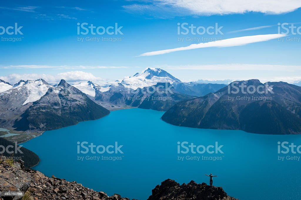 Hiker with his arms outstretched overlooking a glacial lake stock photo