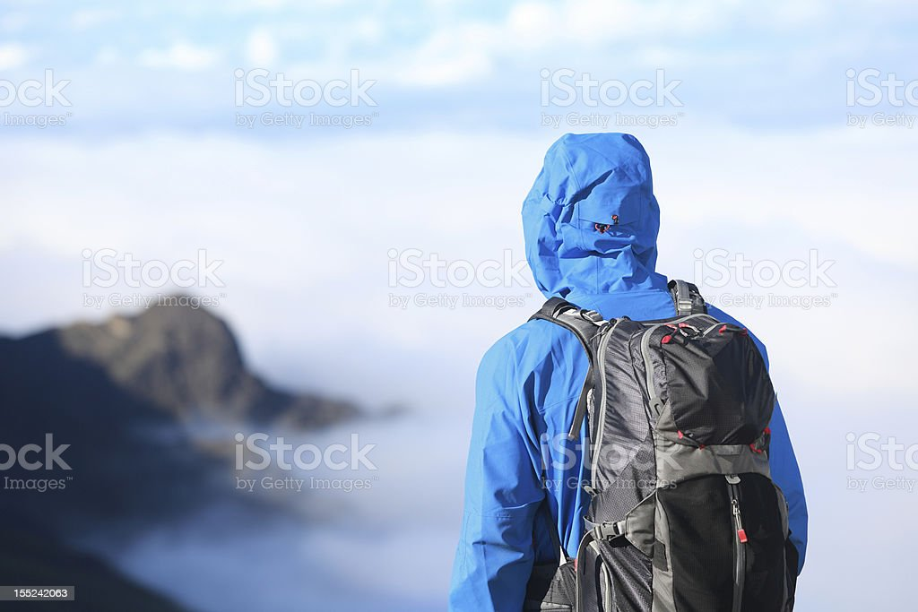 A hiker with his hood up enjoying the view stock photo