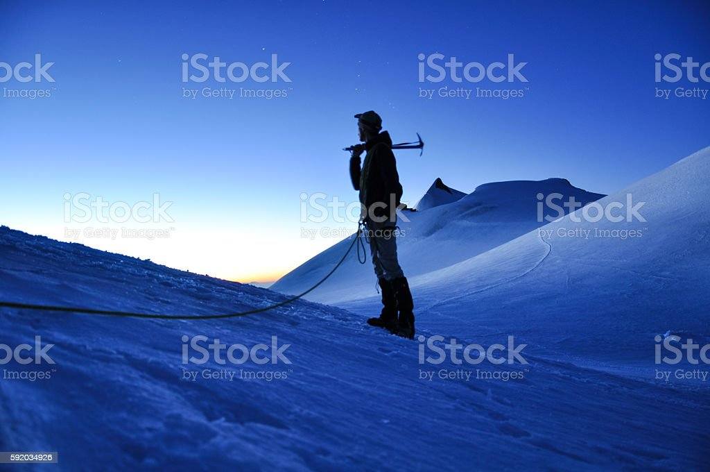 Hiker with ice axe in the Swiss Alps at dawn stock photo