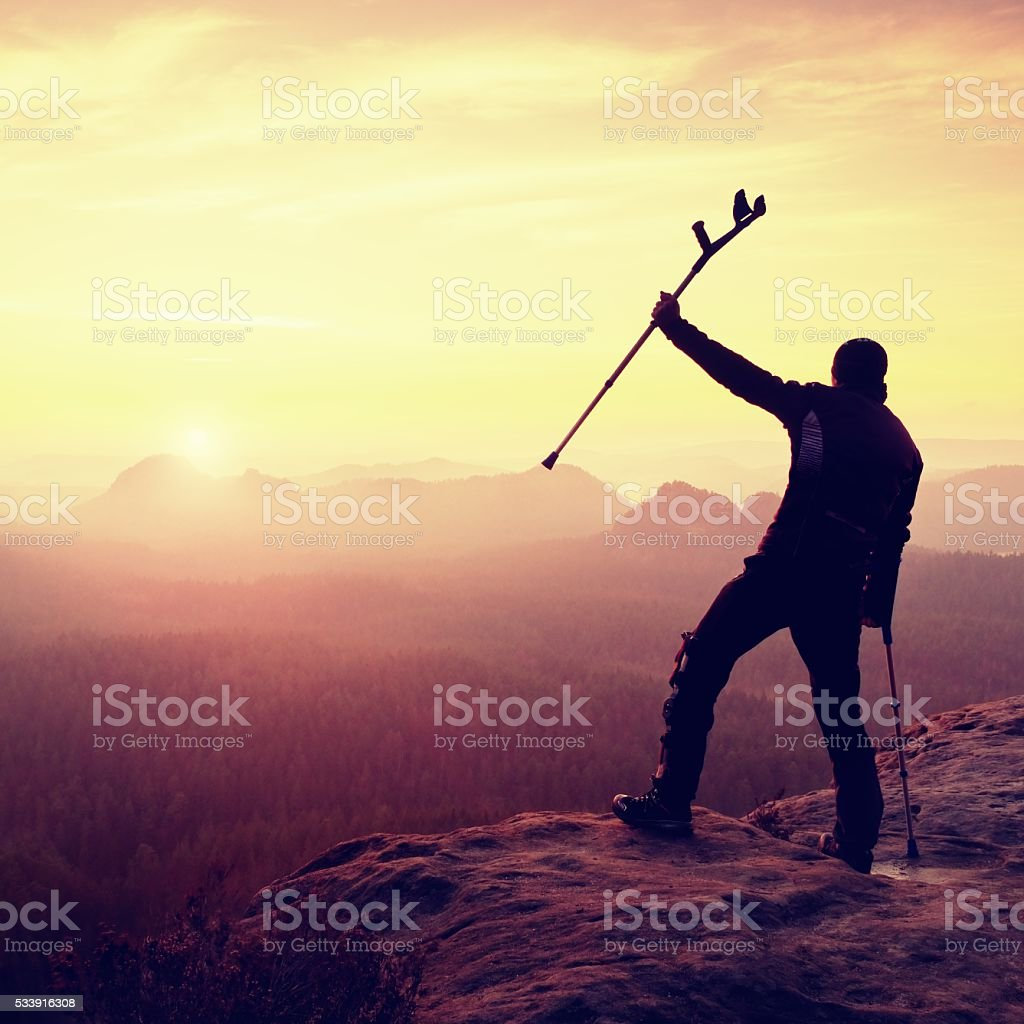 Hiker with  medicine crutch above head achieved mountain peak. stock photo