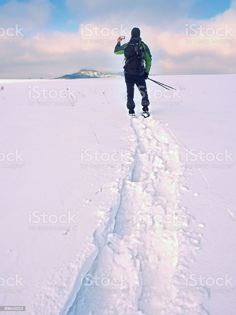Hiker with snowshoes and backpack take photos by smartphone. stock photo
