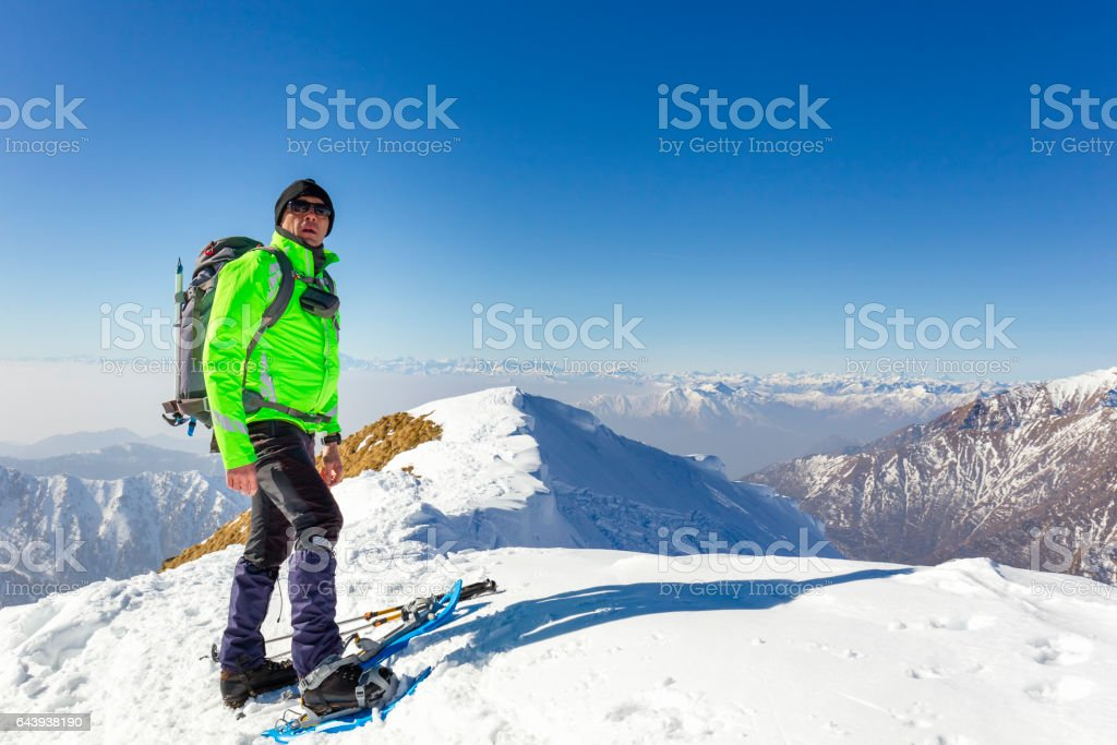 Hiker with snowshoes on top of the mountain stock photo