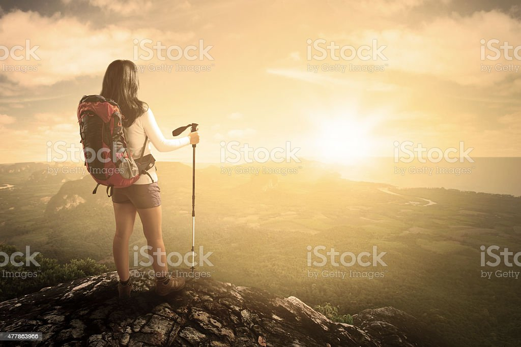 Hiker with stick on mountain stock photo