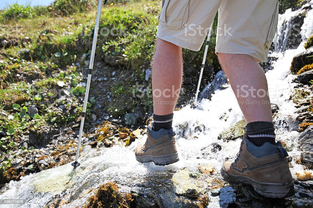 Hiker with Trekking Poles Crossing Mountain Stream in Summer stock photo