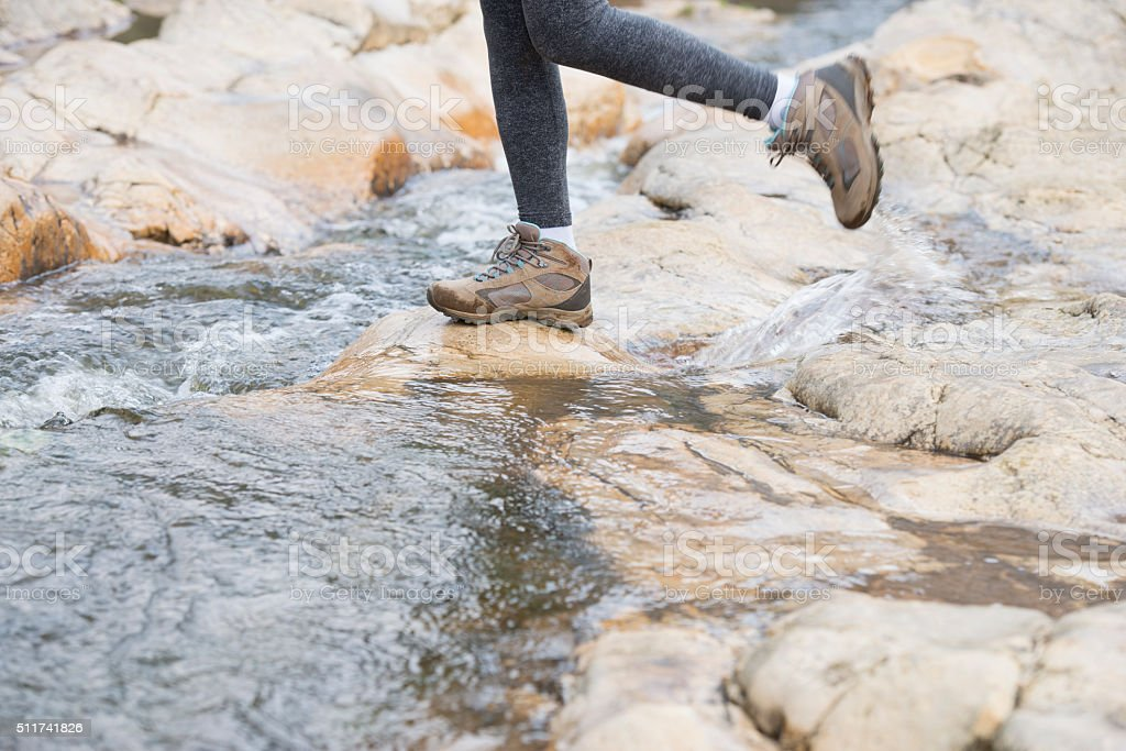 Hiker woman crossing a river. stock photo