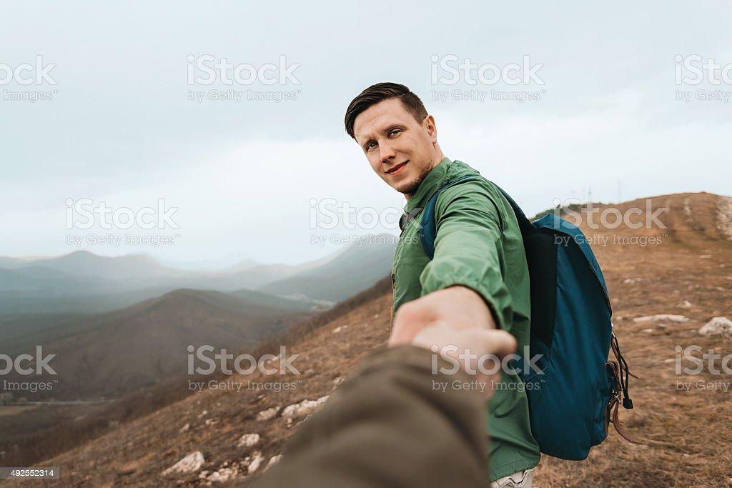 Hiker woman follows a man on nature stock photo
