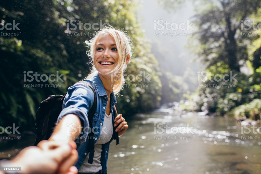 Hiker woman holding man's hand on a nature hike stock photo