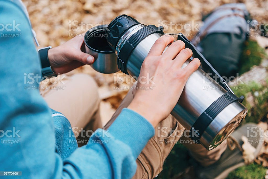 Hiker woman pours tea from thermos to cup outdoor stock photo