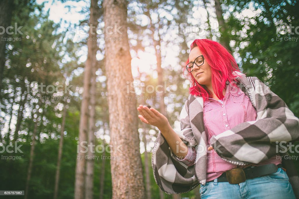 Hiker woman searching direction with a compass outdoor stock photo