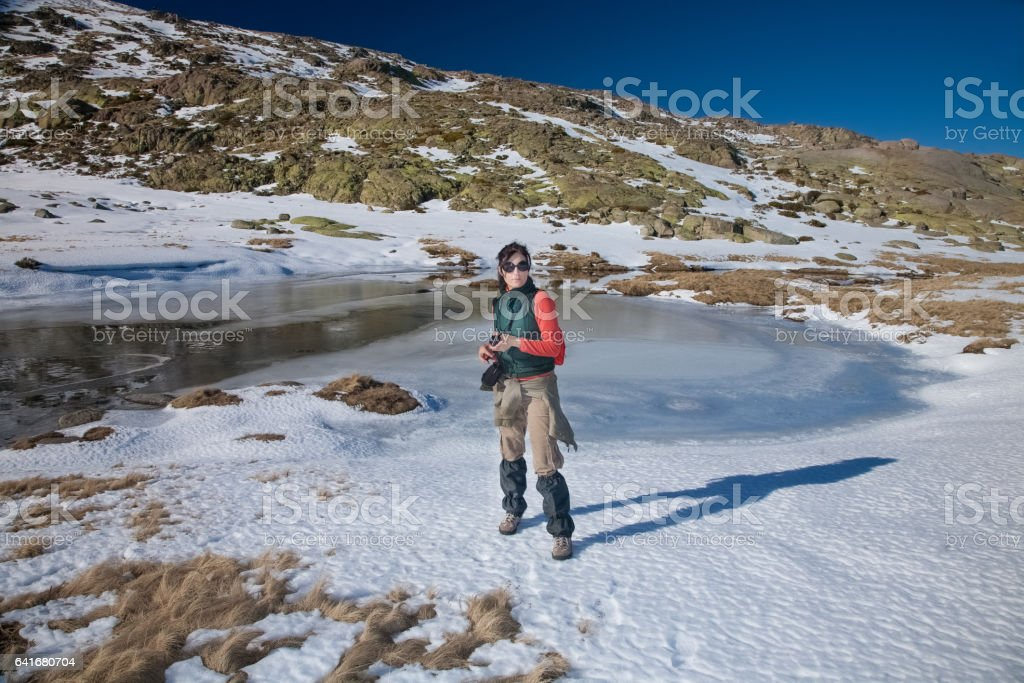 hiker woman standing in winter snow stock photo