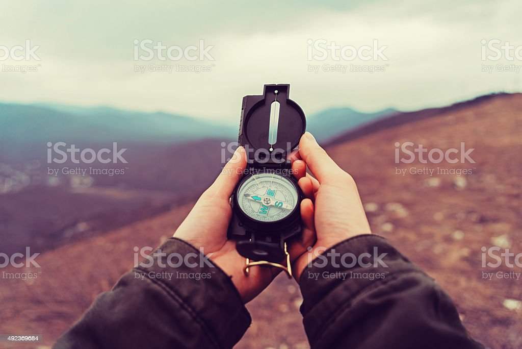 Hiker woman with a compass in the mountains stock photo