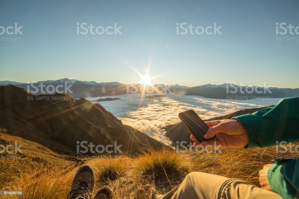 Hikers above the clouds using mobile phone stock photo