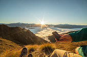 Hikers above the clouds using mobile phone