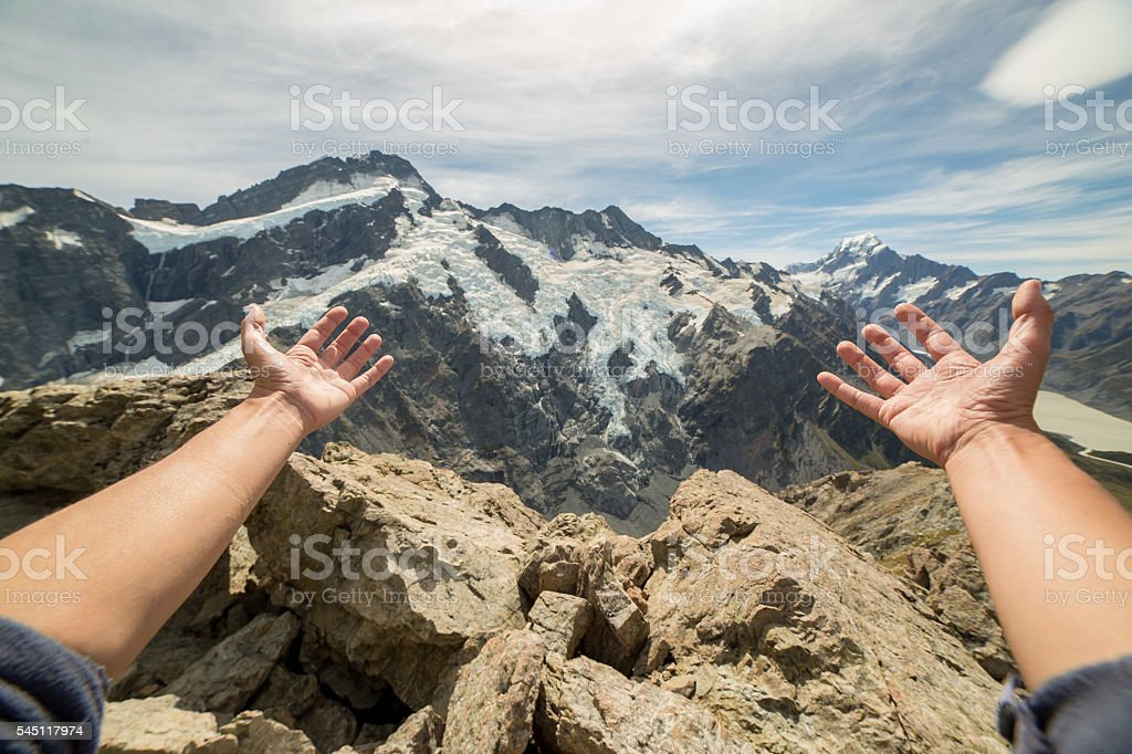 Hikers arms stretches towards the Mount Cook, New Zealand stock photo