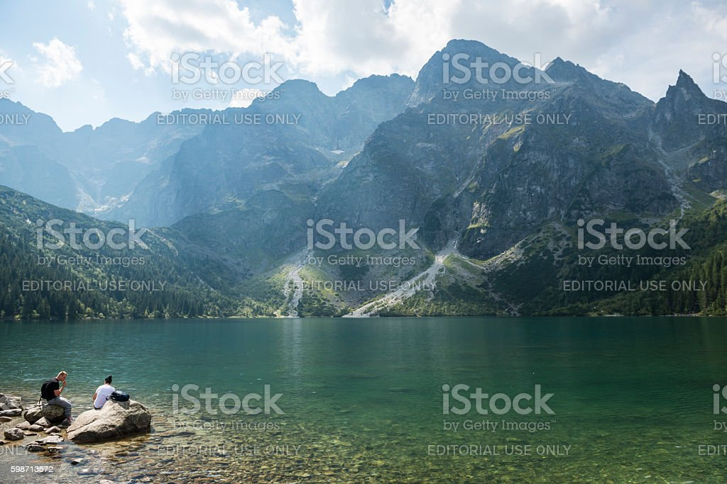 Hikers at Morskie Oko lake in Poland stock photo