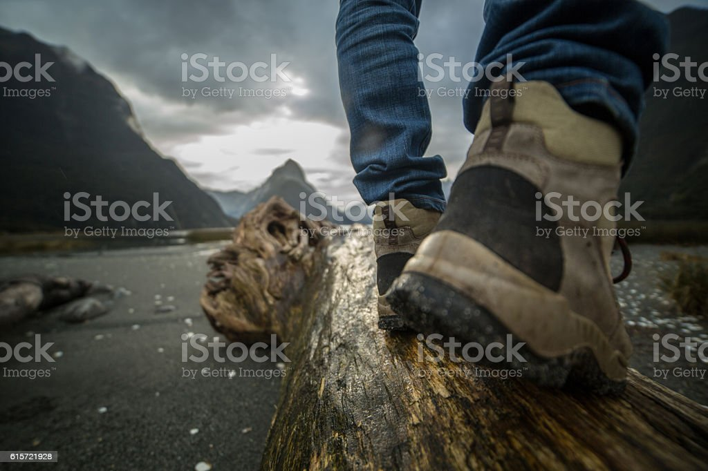 Hiker's boots on tree log, mountains on background stock photo
