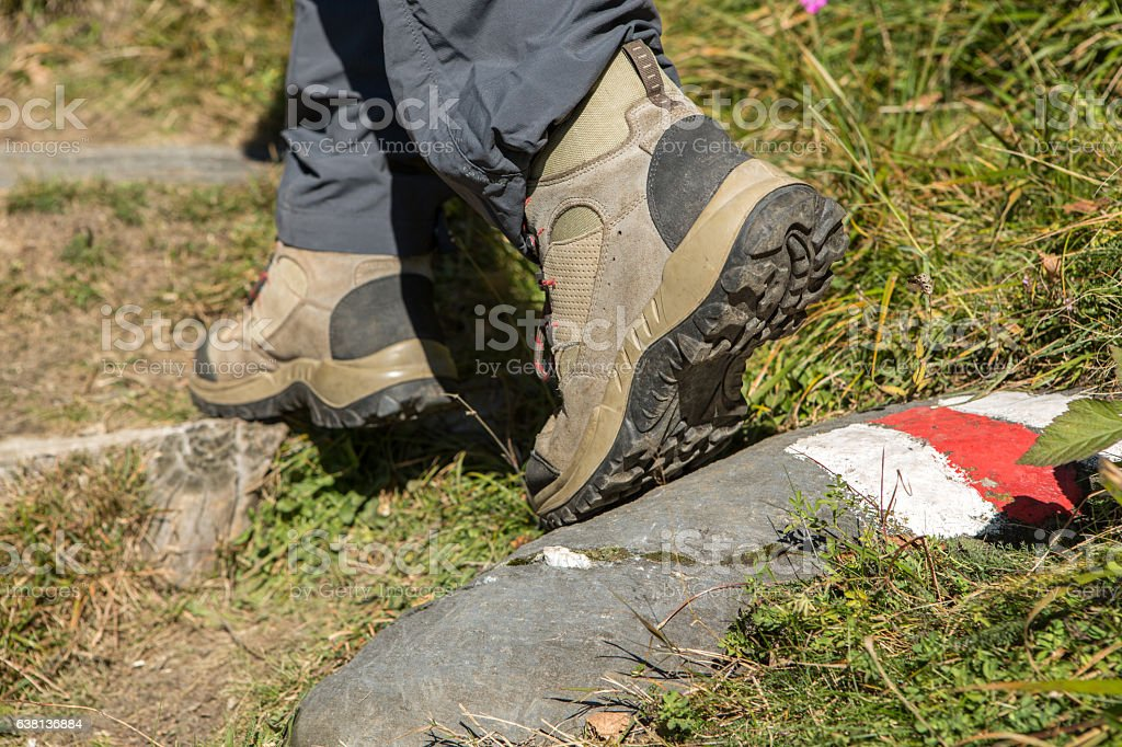 Hiker's boots stepping on painted mark on nature trail stock photo