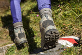 Hiker's boots stepping on painted mark on nature trail