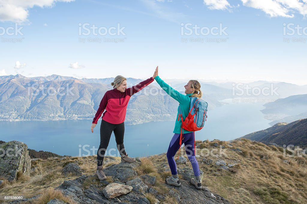 Hikers celebrating at mountain top stock photo