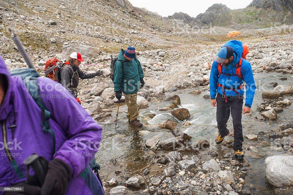 Hikers cross stream stock photo