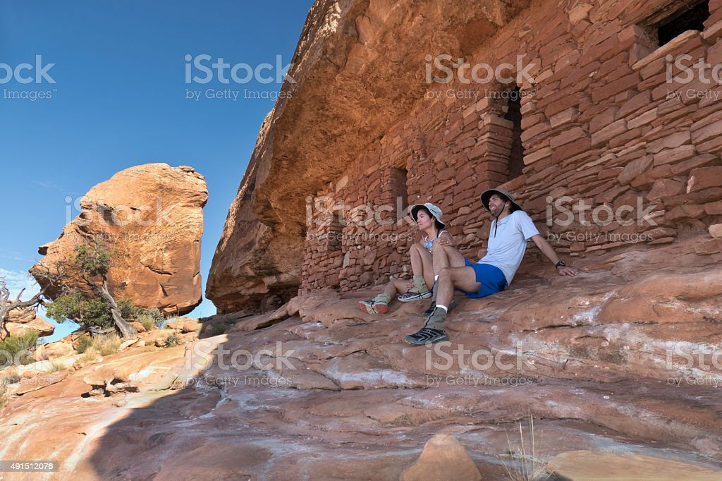 Hikers enjoy view from ancient Cedar Mesa Pueblo ruins Utah stock photo