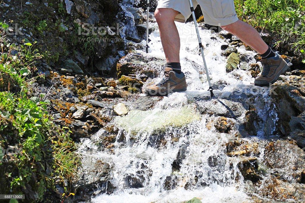 Hiker's Feet Crossing Mountain Stream in Swiss Alps stock photo
