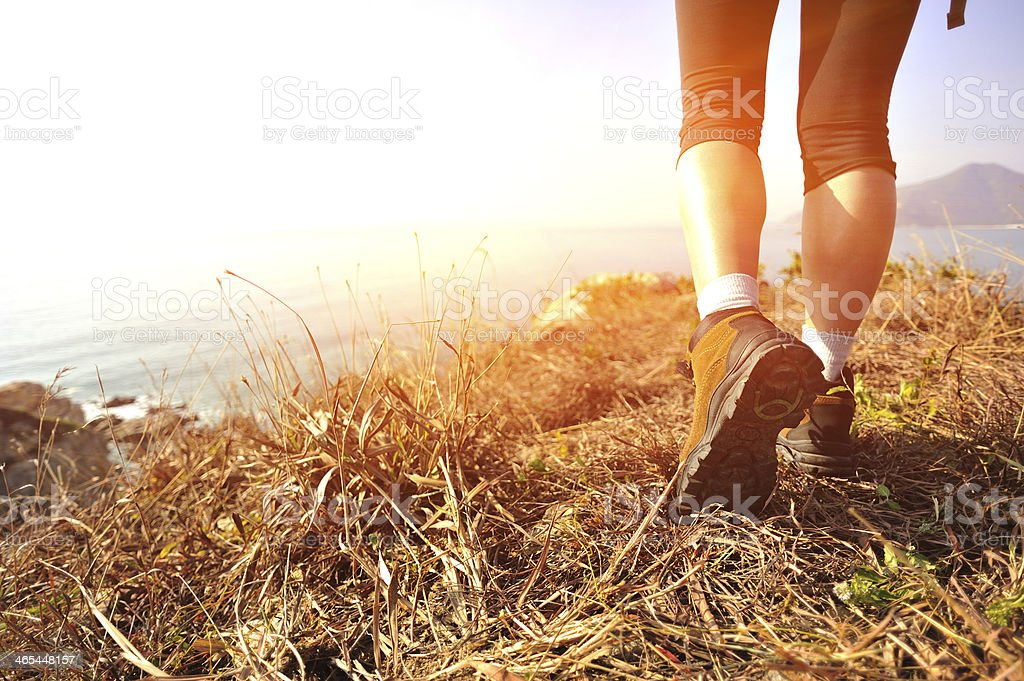 A hiker's feet on high ground above the coastline stock photo