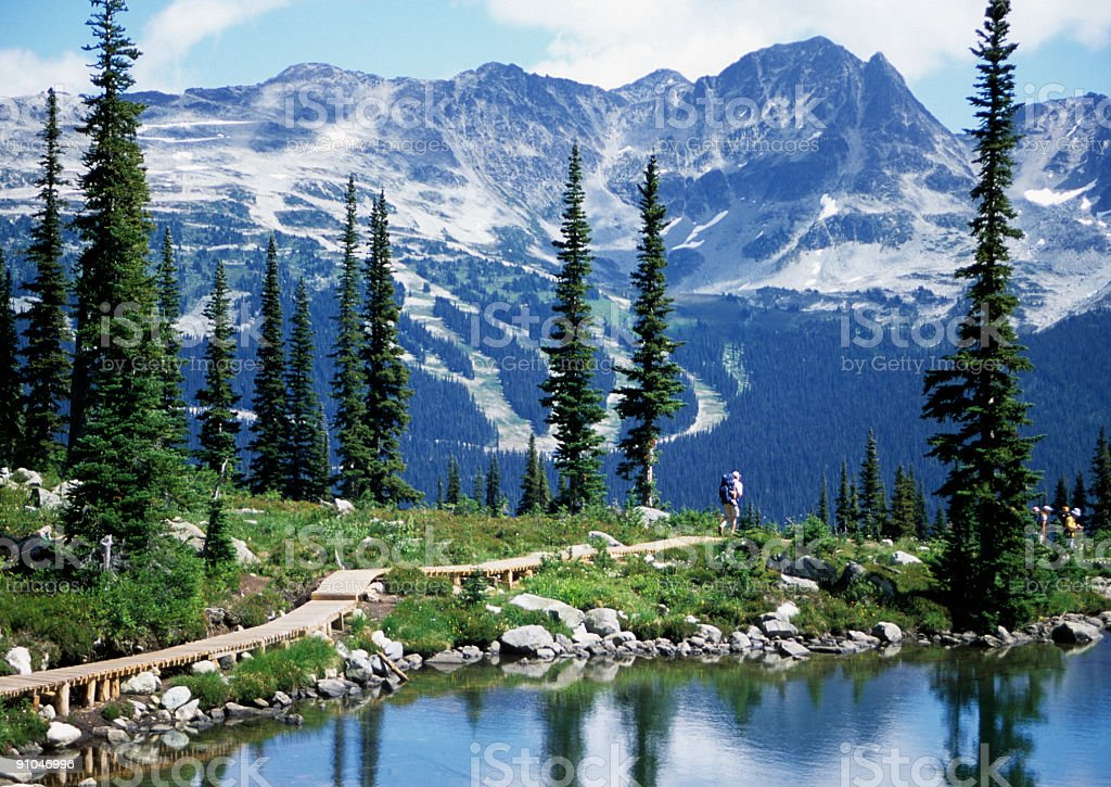 Hikers going to beautiful snow covered mountain stock photo