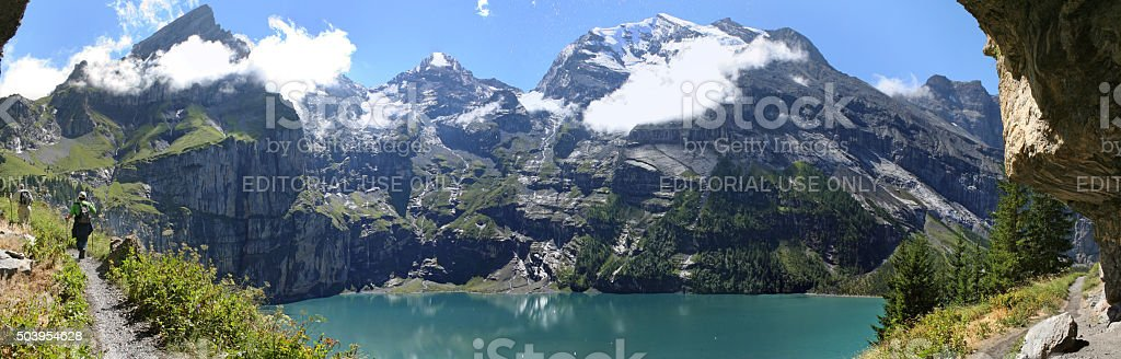 Hikers high above Lake Oeschinensee in the Swiss Alps. stock photo