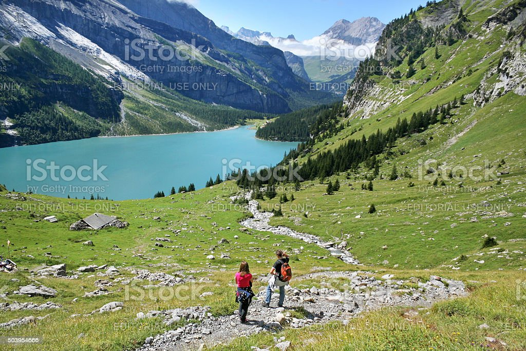 Hikers high above lake Oeschinensee in the Swiss Alps stock photo