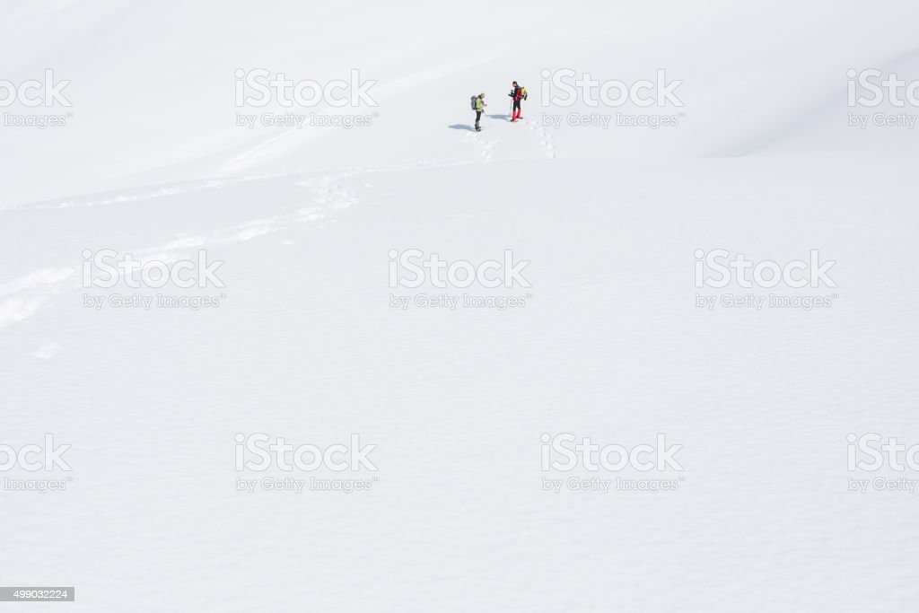 Hikers in snow-covered field at high altitude stock photo