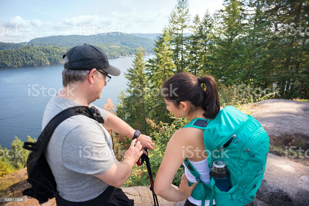 Hikers in Wilderness Forest Using Smart Watch to Track Location stock photo