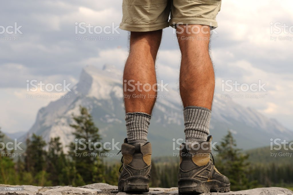 Hiker's Legs Overlooking Forest and Mountain stock photo