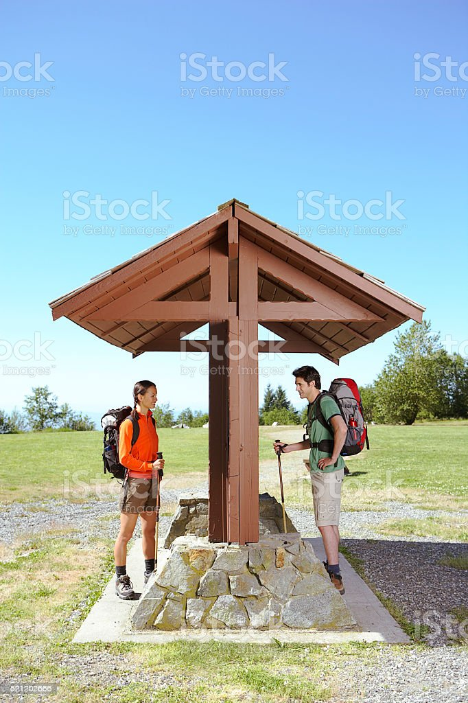 Hikers looking at outdoor information wall stock photo