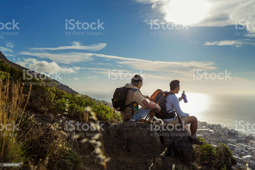 Hikers looking at sea while sitting on rocks stock photo