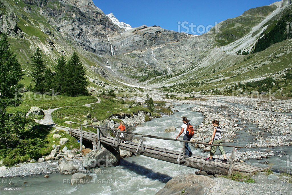 Hikers on a foot bridge in rugged alpine landscape stock photo