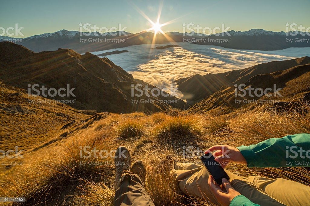 Hikers on mountain top text messaging stock photo
